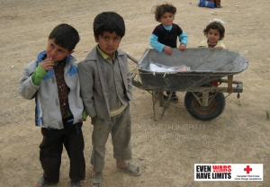 About one hundred Afghan men and children were present to receive cooking supplies, flour and blankets. The items were quite heavy.     In this photo, children are guarding one of the few wheelbarrows that were available while an elder waited in a supply line that was demarcated by barbed wire.