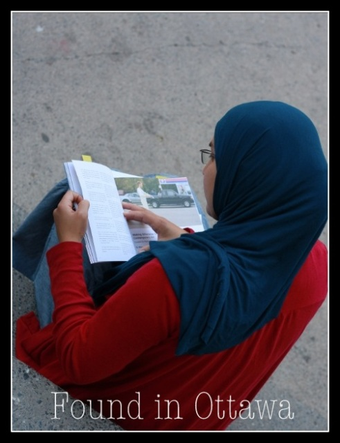 Yumna Rashid sits outside the Islam Care Centre as she reads Herd Magazine